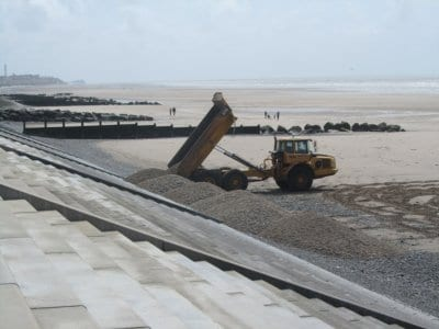 Tipping shingle out of the dumper truck against the steps on Cleveleys beach