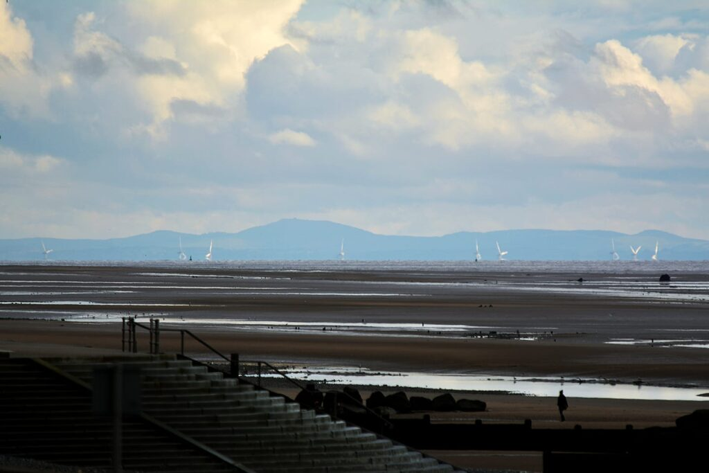 View of the hills of North Wales and wind farm, with Cleveleys beach in the foreground