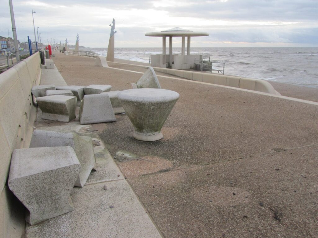 Heavy concrete picnic tables picked up and thrown along the prom, caused by storms, sea coming over and flooding